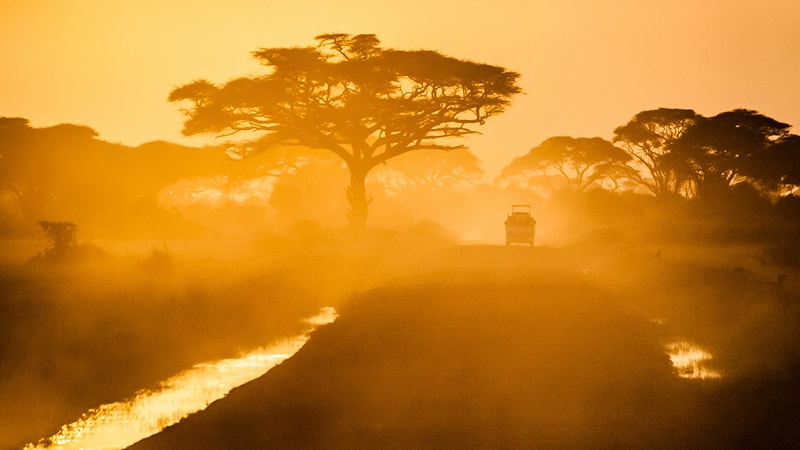 A dusty scene of a road on the Kenyan landscape to depict the modelled electrification of Kenya through the Global Electrification Platform